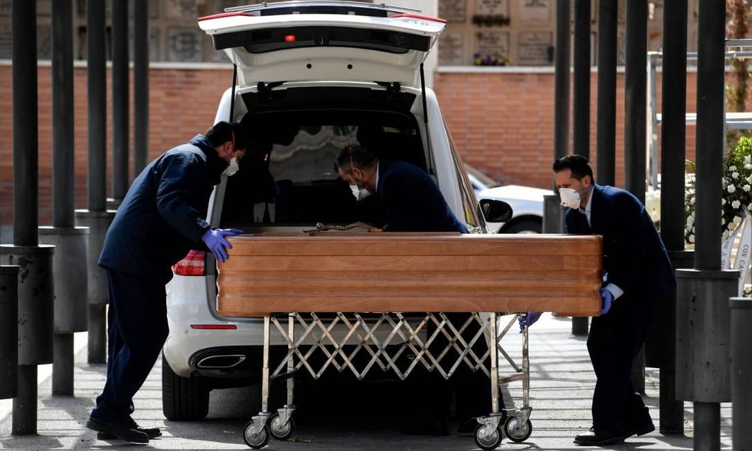 x87625735 Mortuary employees wearing face masks wheel a coffin into the crematorium of La Almuden.jpg.pagespeed.ic .tFqvX9cSQq