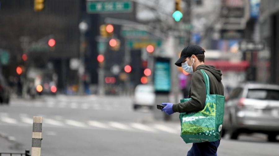 5abr2020 homem usa luvas e mascara de protecao contra o novo coronavirus ao carregar sua sacola reutilizavel de compras em nova york eua