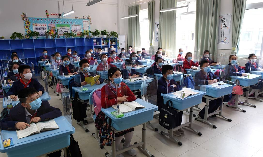 x87968324 Students wearing face masks sit in a classroom with partitions on their desks as more s.jpg.pagespeed.ic .aZZAi9YlEU