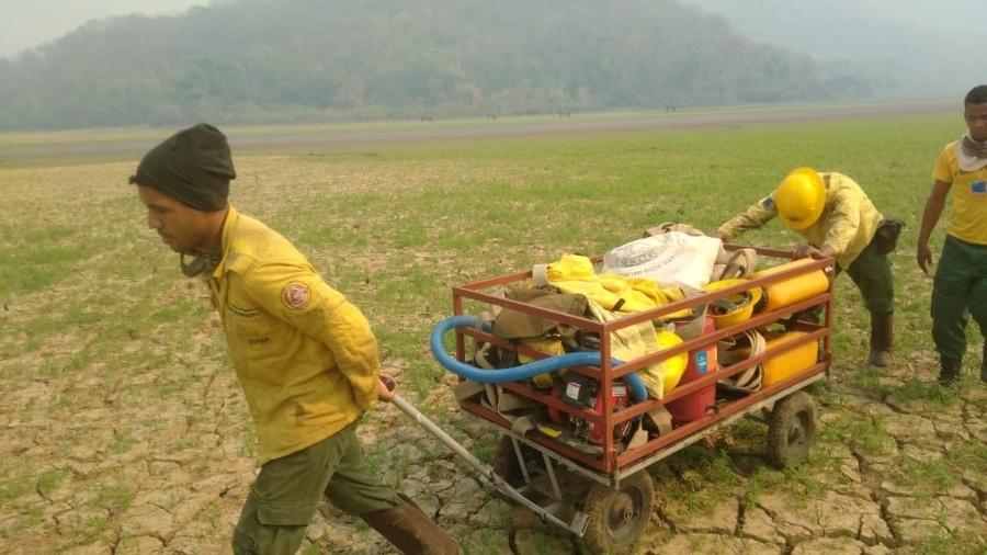 brigadistas do prevfogo empurram carrinho com equipamentos para combater incendio na serra do amolar no pantanal do ms em setembro de 2020