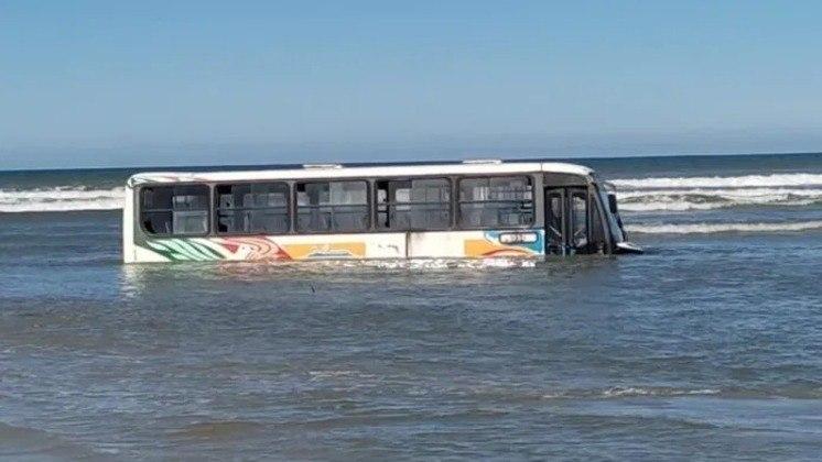 Após ressaca, ônibus fica encalhado em praia, é encoberto pelo mar e precisa de tratores para ser removido