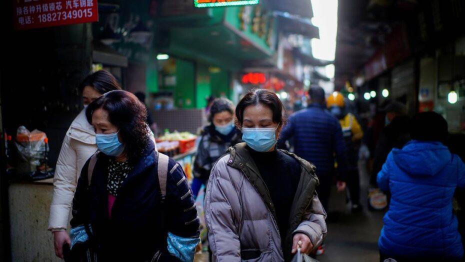 x FILE PHOTO People wearing face masks walk on a street market following an outbreak of t jpg pagespeed ic xewgqFj